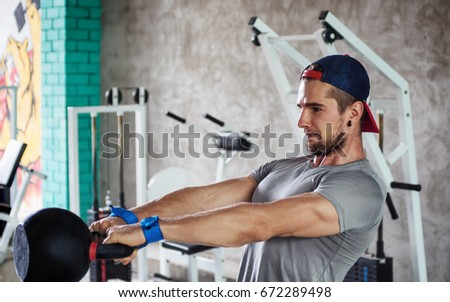 young muscular athlete lifting weight in gym. Fitness, Bodybuilding concept. Blurred Exercise equipment in background. Text space