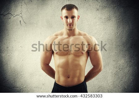 Young muscular bare-chested man is standing with hands behind his back over concrete wall background