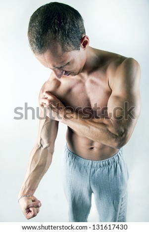 young muscular bodybuilder holding his arm tight with big veins