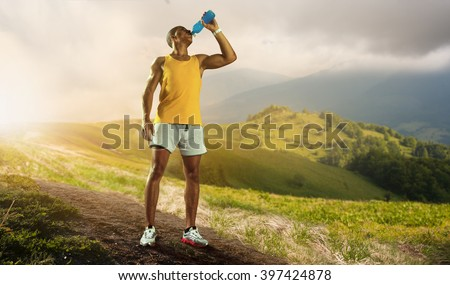 Young muscular build man drinking water of bottle after running,  - stock photo
