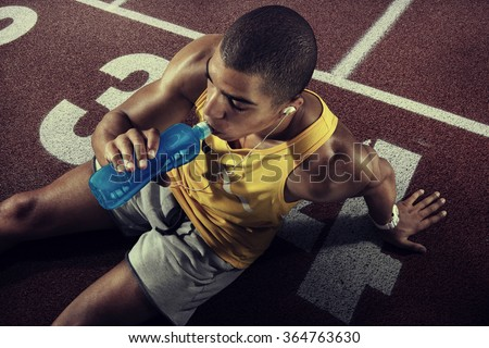 Young muscular build man drinking water of bottle after running, attractive athlete resting after workout outdoors, fitness and healthy lifestyle concept. Start line - stock photo