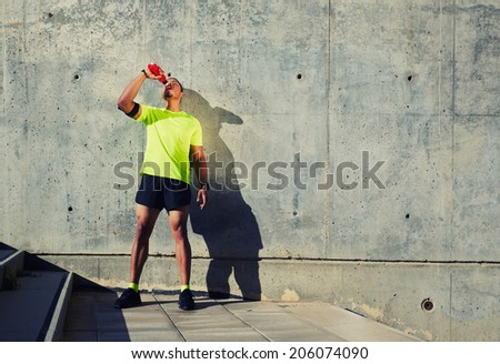 Young muscular build man with running armband on the arm drinking water of bottle,  attractive athlete resting after workout outdoors, fitness and healthy lifestyle concept - stock photo