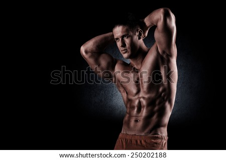young muscular guy in the studio, posing for the camera - stock photo