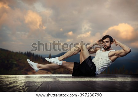 young muscular man does exercising  on outdoor at sunset - stock photo