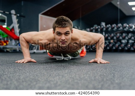 young muscular man doing exercises in gym