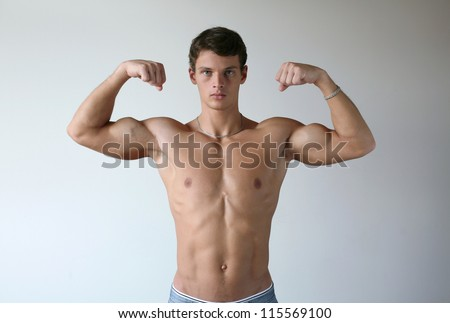 Young muscular man flexing his biceps - stock photo