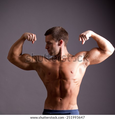 young muscular man flexing his muscles