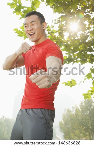 Young Muscular Man in a Fighting Stance - stock photo