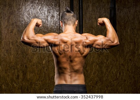 Young muscular man in gym doing exercise. Showing his back muscles.