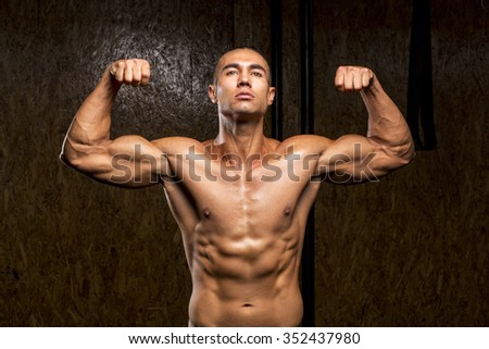 Young muscular man in gym doing exercise. Showing his muscles.