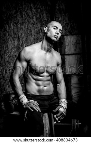 Young muscular man in gym doing exercise. Showing his muscles. Black and white
