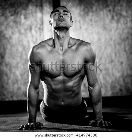 Young muscular man in gym doing exercise. Showing his muscles. Black and white - stock photo
