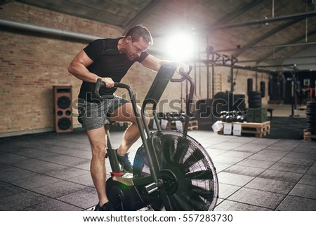 Young muscular man in sportswear sitting on cycling machine and riding fast in modern gym.