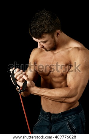 Young muscular man is engaged with the expander
