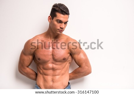 Young muscular man is standing on white background and looking down.