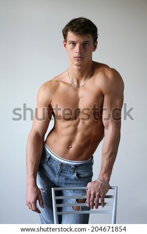 Young muscular man leaning on the chair - stock photo