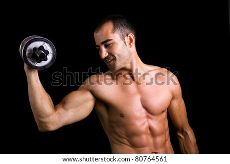 Young muscular man lifting dumbbells against black background
