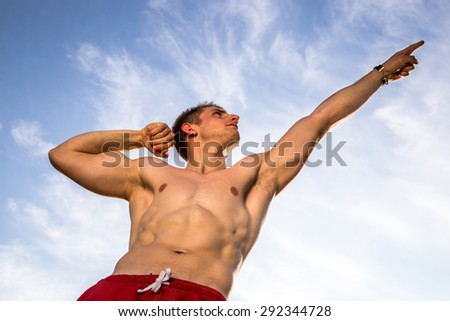 young muscular man pointing at sky
