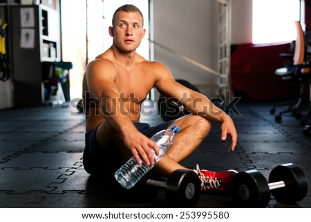 Young muscular man resting after gym workout - stock photo