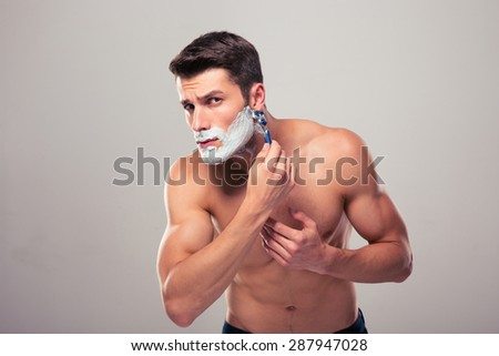 Young muscular man shaving over gray background and looking at camera - stock photo