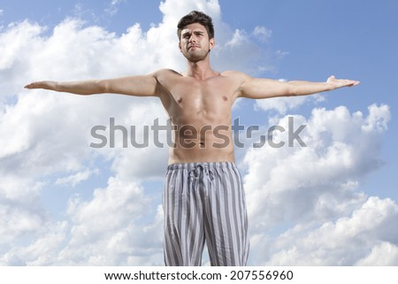 Young muscular man standing arms outstretched against cloudy sky - stock photo