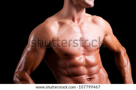 Young muscular man with beautiful torso agaisnt black background