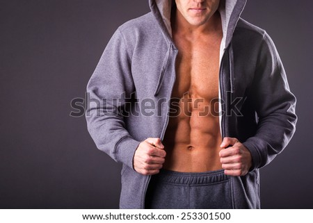 Young muscular man with open jacket revealing muscular chest and abs.Portrait of a muscular young man in hood jacket posing on black background.Young man with athletic body posing on black background - stock photo