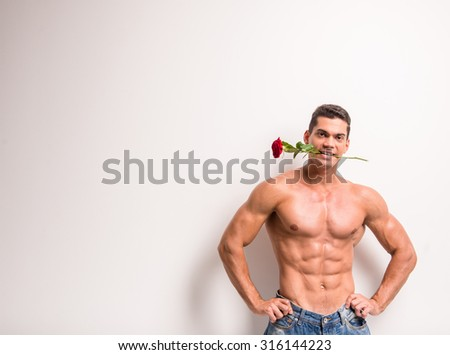 Young muscular man with perfect torso is holding single rose in his tooth while standing against white background.