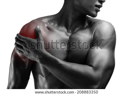 young muscular man with shoulder pain , isolated on white background, monochrome photo - stock photo