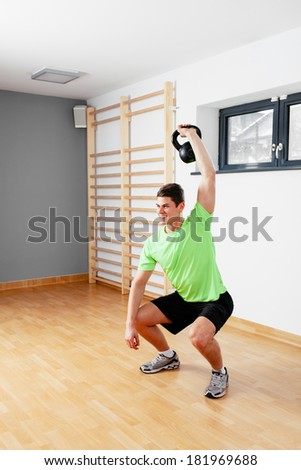 Young muscular man working out with weights