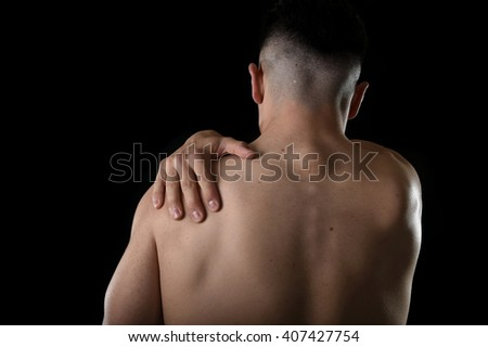 young muscular sport man holding sore shoulder with hand touching or massaging in workout stress body pain and health problem isolated on black background - stock photo
