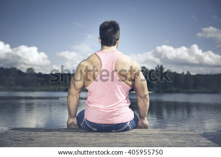 young muscular sports man back side at the lake