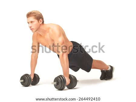 Young muscular sportsman making push-ups with straight arms on black dumbbells, looking straight forward, isolated on white background, dressed in black shorts and black sneakers. Full length portrait