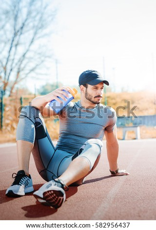 Young muscular sportsman take a little break after hard training outdoors. Fitness, sport, lifestyle concept