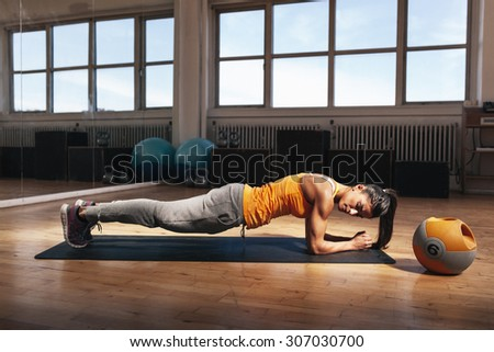 Young muscular woman doing core exercise on fitness mat in the gym. Fit female doing press-ups during the training in the health club. - stock photo