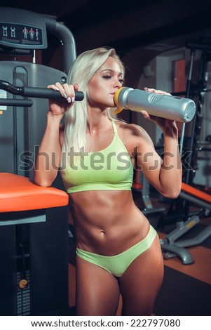 Young muscular woman drinking sports nutrition - stock photo