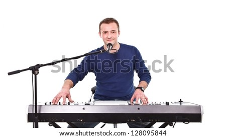 Young musician behind synthesizer and microphone preparing for concert - stock photo