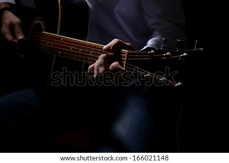 Young musician playing acoustic guitar, close up, on dark background - stock photo