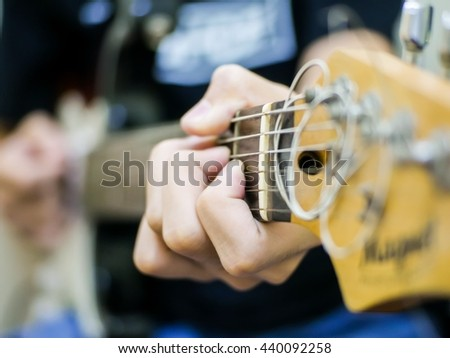 Young musician playing acoustic guitar close up. Soft focus. - stock photo