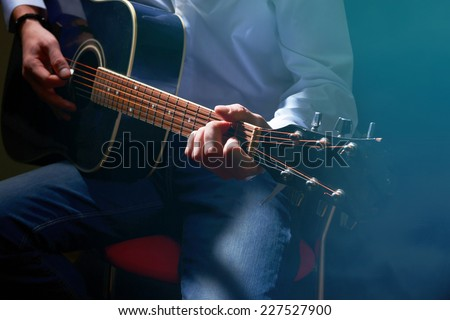Young musician playing acoustic guitar on dark background - stock photo