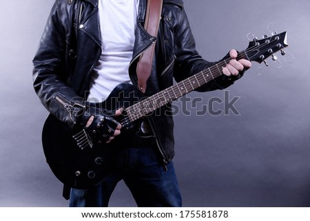 Young musician playing  guitar and singing, on dark color background - stock photo
