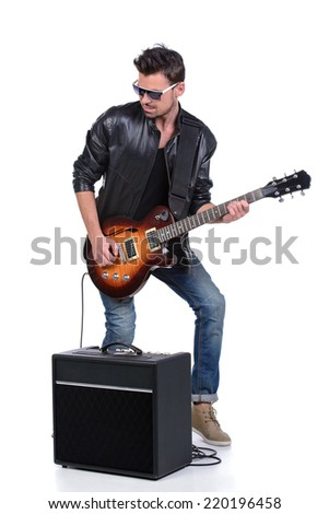 Young musician playing guitar, isolated on white - stock photo
