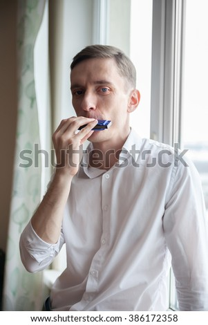 Young musician playing    harmonica at window