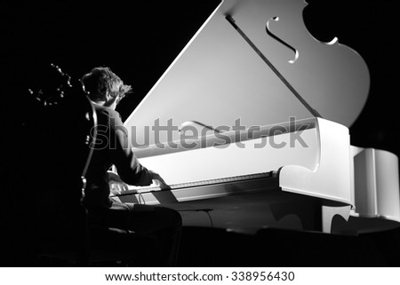 Young musician playing the grand piano - stock photo