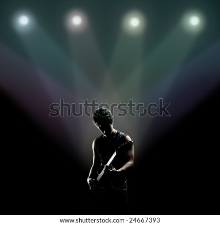 young musician playing the guitar on the stage - stock photo
