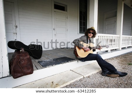 Young musician sitting on the porch of an abandoned house.