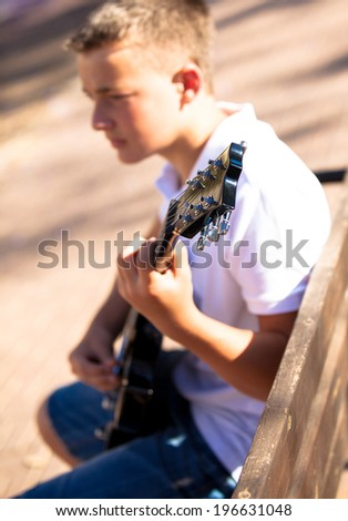 young musician with a guitar on a sunny day