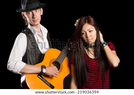 Young musicians performing a song. Interracial young couple, Asian woman and Caucasian man.