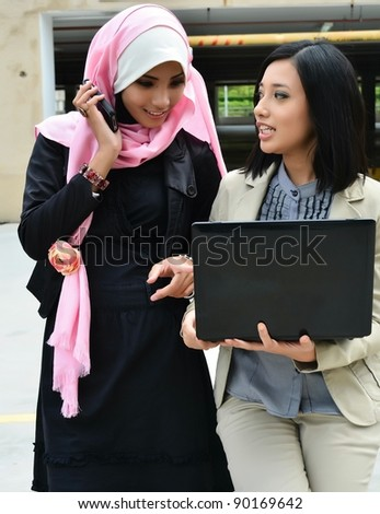 young muslim business woman in head scarf with cell phone and laptop - stock photo