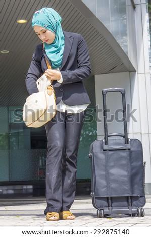 Young Muslim business woman looking at her handbag - stock photo